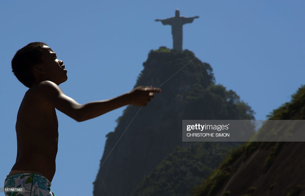 A boy plays with a kite on the roof of the church of Santa Marta slum, in Rio de Janeiro, Brazil, on December 05, 2012.
