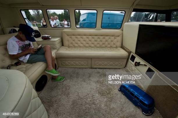 A boy plays with a tablet inside a Kombi during an exhibition at the Volkswagen plant in Sao Bernardo do Campo southern Sao Paulo Brazil on December...