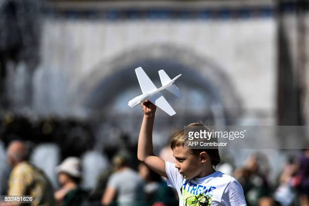 A boy plays with a toy plane made of foam plastic at the AllRussia Exhibition Centre a trade show and amusement park in Moscow on August 16 2017 /...