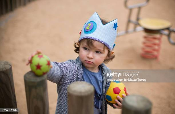 boy plays with balls wearing a crown