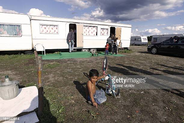 A boy plays with his bicycle during the visit of Versailles bishop Eric Aumonier in a Roma camp on August 28 2010 in CarrieressousPoissy west of...