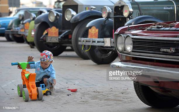 A boy plays with his toys in front of vehicles during the fifth edition of the ''Peking to Paris Motor Challenge 2013'' in Kiev on June 20 2013 The...