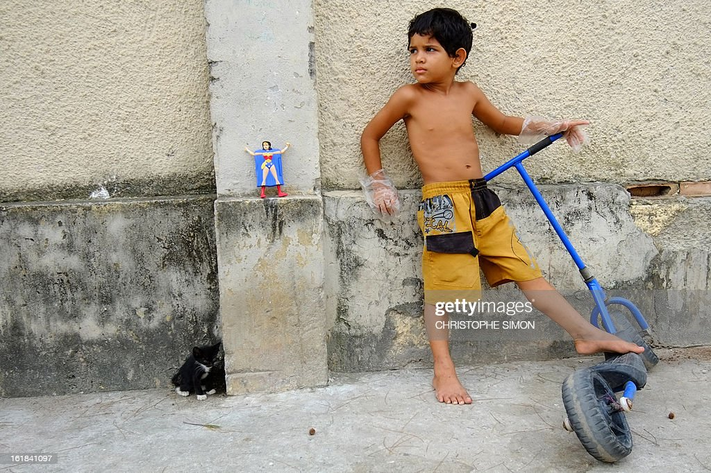 A boy plays with scooter in a street of the Cidade de Deus shantytown, western Rio de Janeiro, Brazil on February 16, 2013. AFP PHOTO/Christophe Simon
