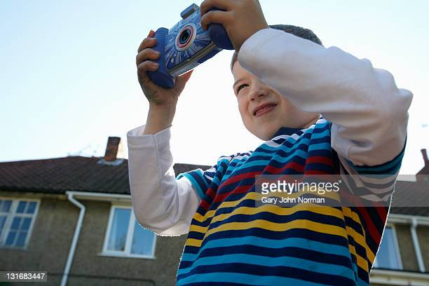 Boy plays with toy camera