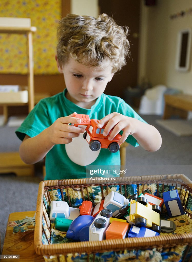 Boy plays with toy cars in basket : Stock Photo