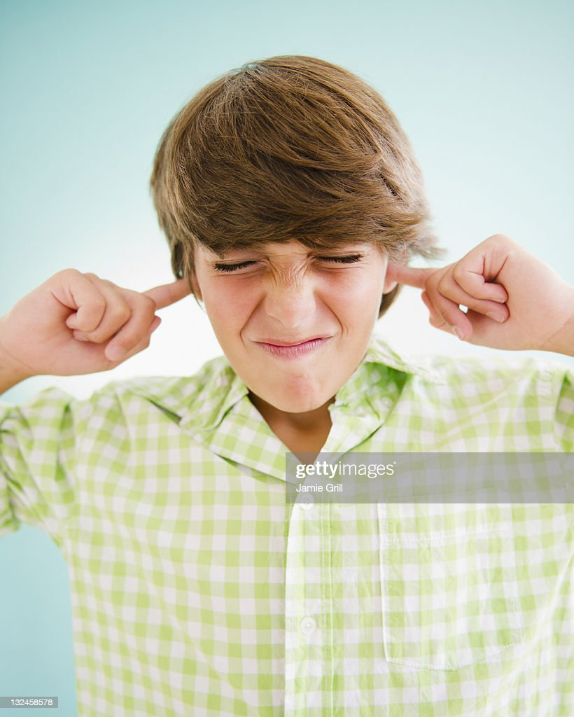 Boy plugging his ears, ignoring : Stock Photo