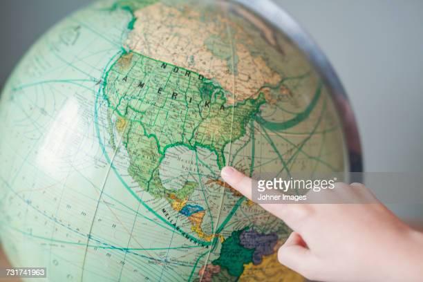 Boy pointing at globe