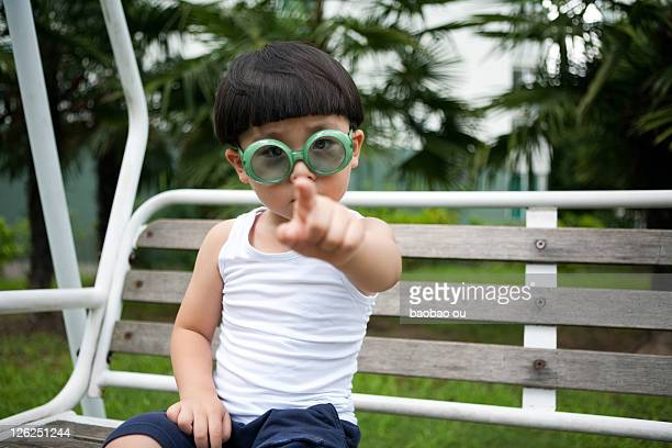 Boy pointing front with funny green sunglass