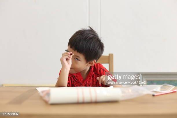 Boy Pointing Pencil While Sitting At Home