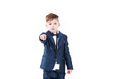 Young serious little boy in suit pointing and looking at the camera isolated on white background