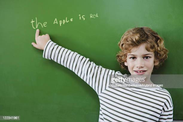 Boy pointing to writing on chalkboard