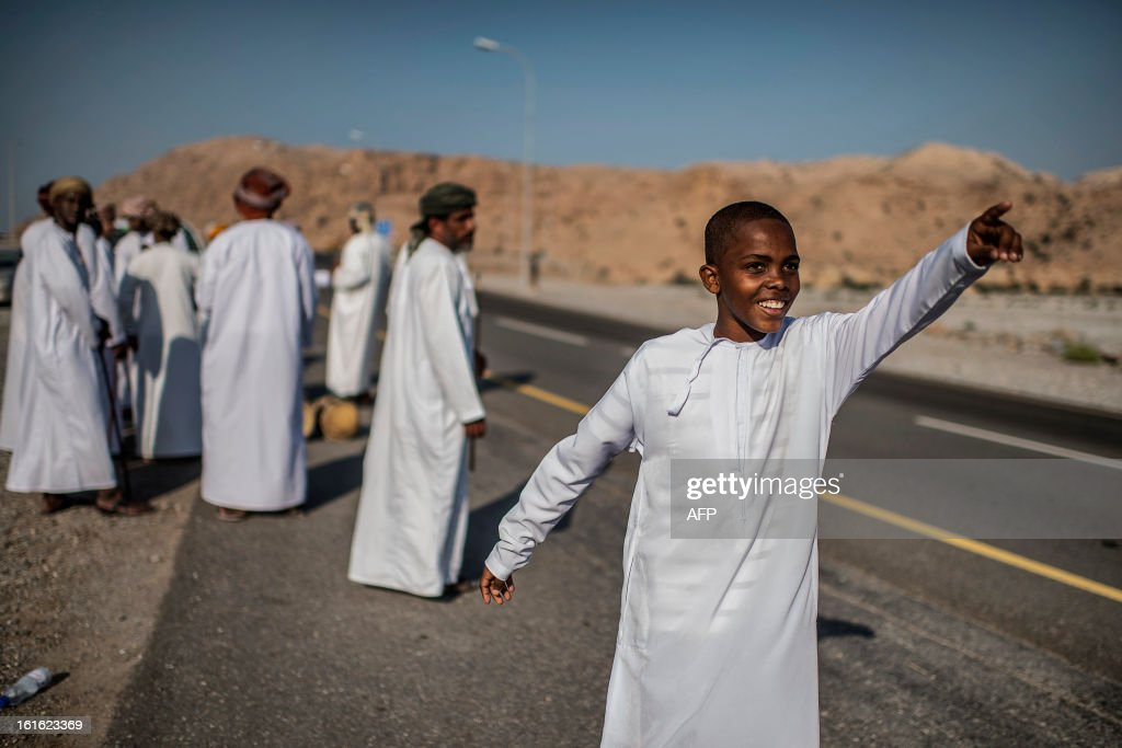 A boy points as Omanis wait for cyclists during the third stage of the Tour of Oman, from Nakhal Fort to Wadi Dayqah Dam, on February 13, 2013, in Oman. The six-stage race, which follows the Tour of Qatar, won by Britain's Mark Cavendish last week, culminates on February 16, along the Matra Corniche.