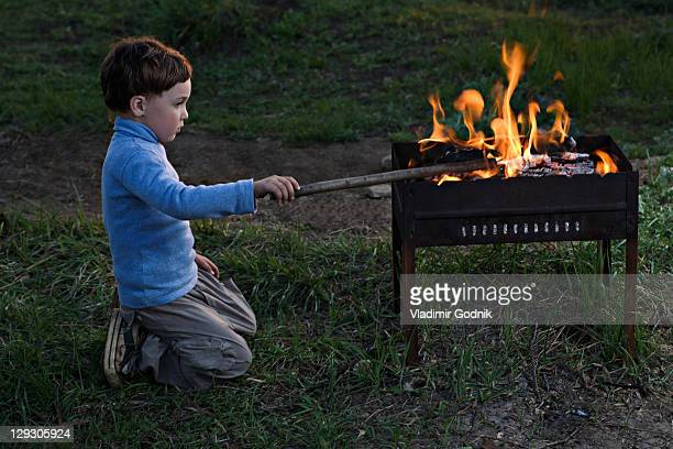 A boy poking at a fire in an outdoor fire pit