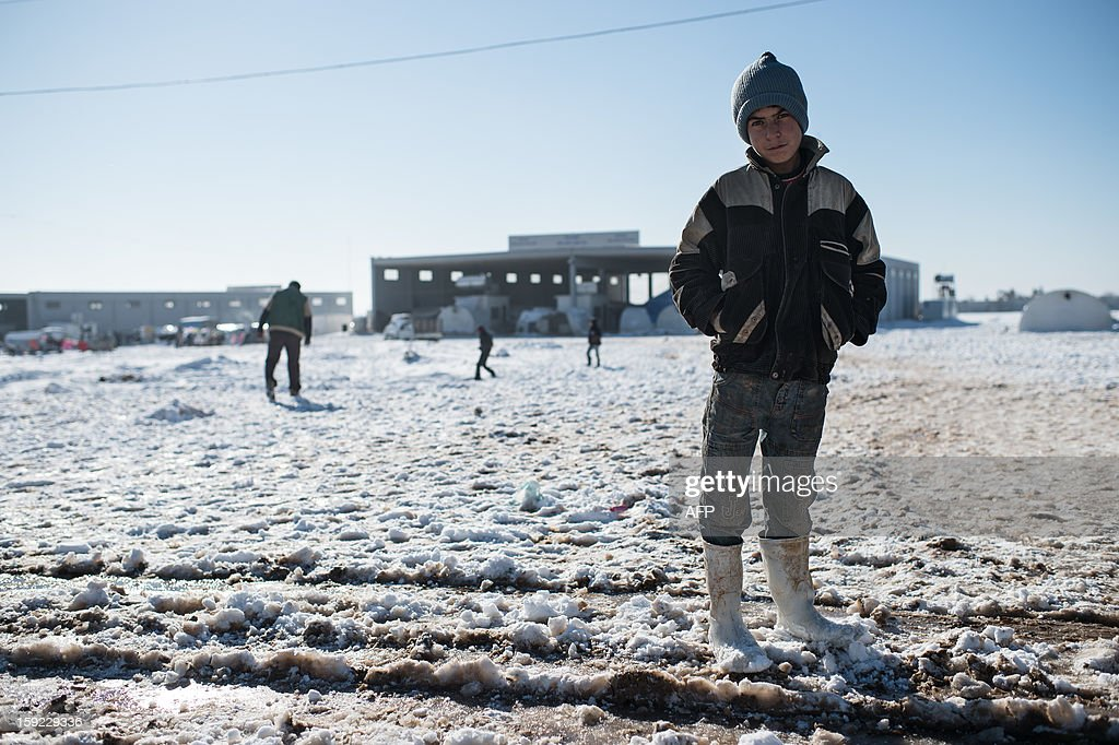 A boy poses after snow falls in a Syrian refugees camp in Azaz, near the Turkish border, on January 10, 2013. Snow carpeted Syria's war-torn cities but sparked no let-up in the fighting, instead heaping fresh misery on a civilian population already enduring a chronic shortage of heating fuel and daily power cuts.