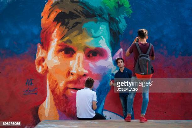 A boy poses for a photo beside a graffiti portraying Barcelona's Argentinian forward Lionel Messi as another one takes photos on June 17 2017 in...