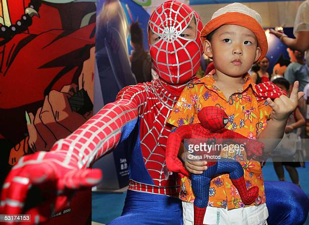A boy poses for a picture with a model dressed as Spiderman at the 2005 Shanghai Animation Fair June 30 2005 in Shanghai China China has a population...