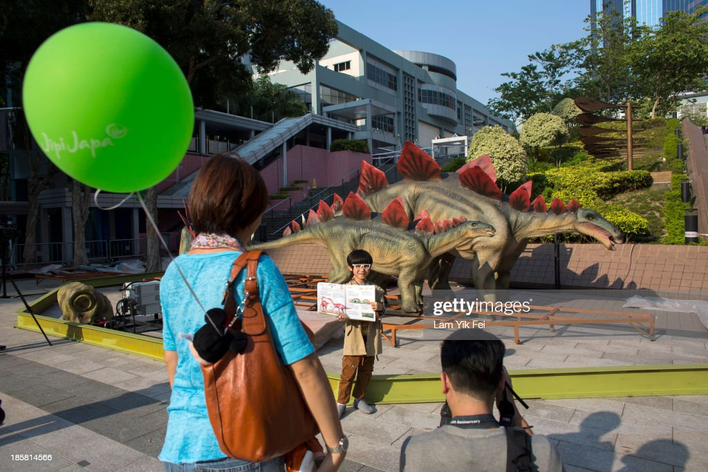 A boy poses for photograph in front of robotic dinosaurs in Hong Kong Science Museum on October 25, 2013 in Hong Kong, Hong Kong. Hong Kong Science Museum has started to set up the exhibits for its upcoming large-scale 'Legends of the Giant Dinosaurs' exhibition. Among the exhibits will be six large robotic dinosaurs specially produced for the exhibition and set to be installed this Friday October 25. These six robotic dinosaurs will be put on display in the piazzas of the museum.