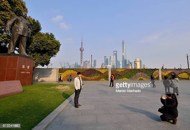 A boy poses for photos with the New Pudong Area the Financial Center of Shanghai with the Oriental Pearl TV Tower in the background on February 25...