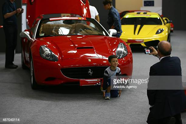 A boy poses in front of a Ferrari California presented during the Supercar Roma Auto Show in Rome capital city of Italy on October 10 2014
