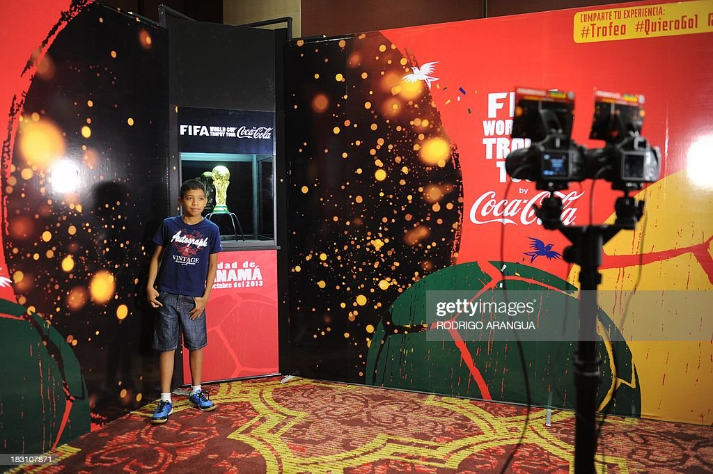 A boy poses next to the FIFA World Cup in Panama City, on October 4, 2013. The Cup is in Panama for two days as part of a tour to exhibit it in 89 countries before the beginning of the FIFA World Cup Brazil 2014. AFP PHOTO/ Rodrigo ARANGUA