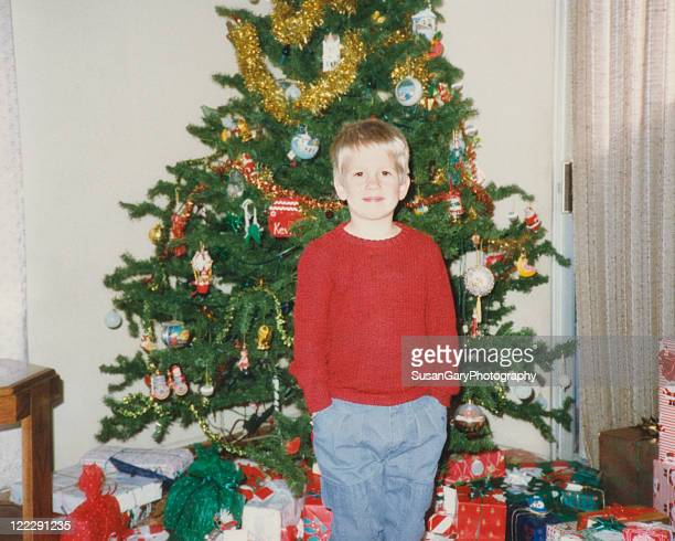 Boy poses with christmas tree