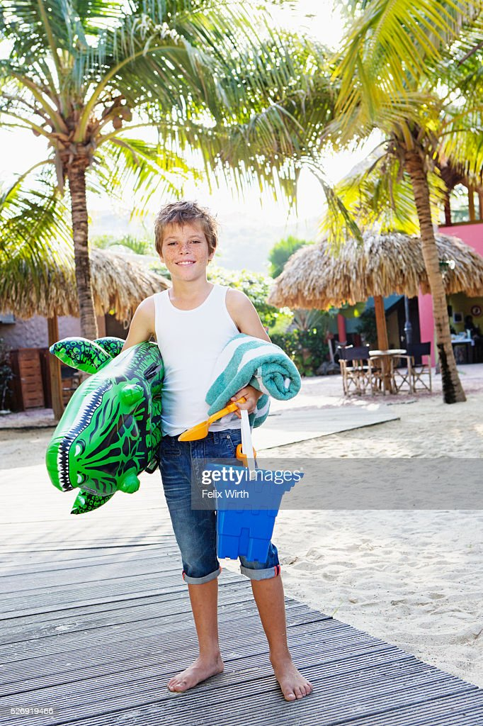 Boy (10-12) posing with beach toys : Stock-Foto