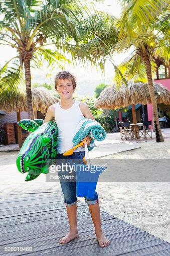 Boy (10-12) posing with beach toys : Stock-Foto