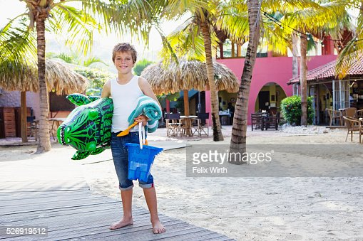 Boy (10-12) posing with beach toys : Photo