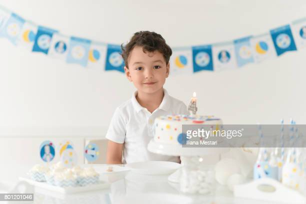 Boy posing with his birthday cake and table