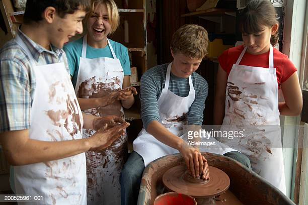 Boy (13-15) potting on wheel surrounded by classmates