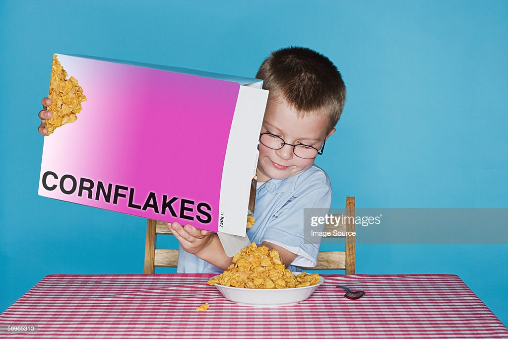 Boy pouring cornflakes : Stock Photo