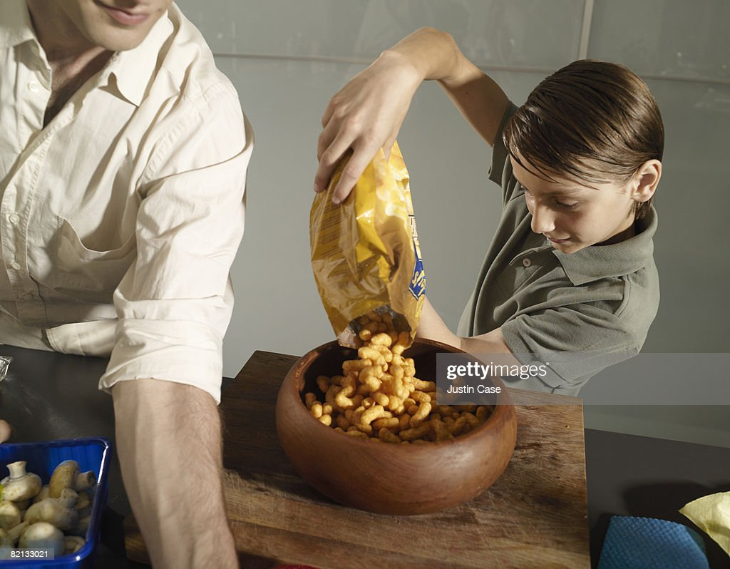 Boy pouring crisps into bowl : Stock Photo