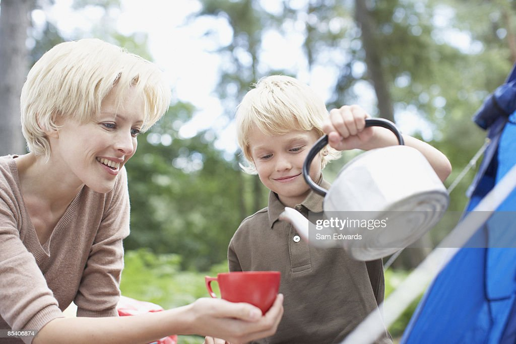 Boy pouring hot water for mother at campsite : Stock Photo