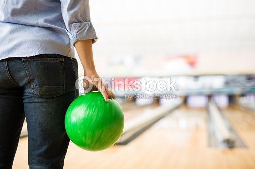 Boy Practicing Bowling With Green Ball In Club Stock Photo