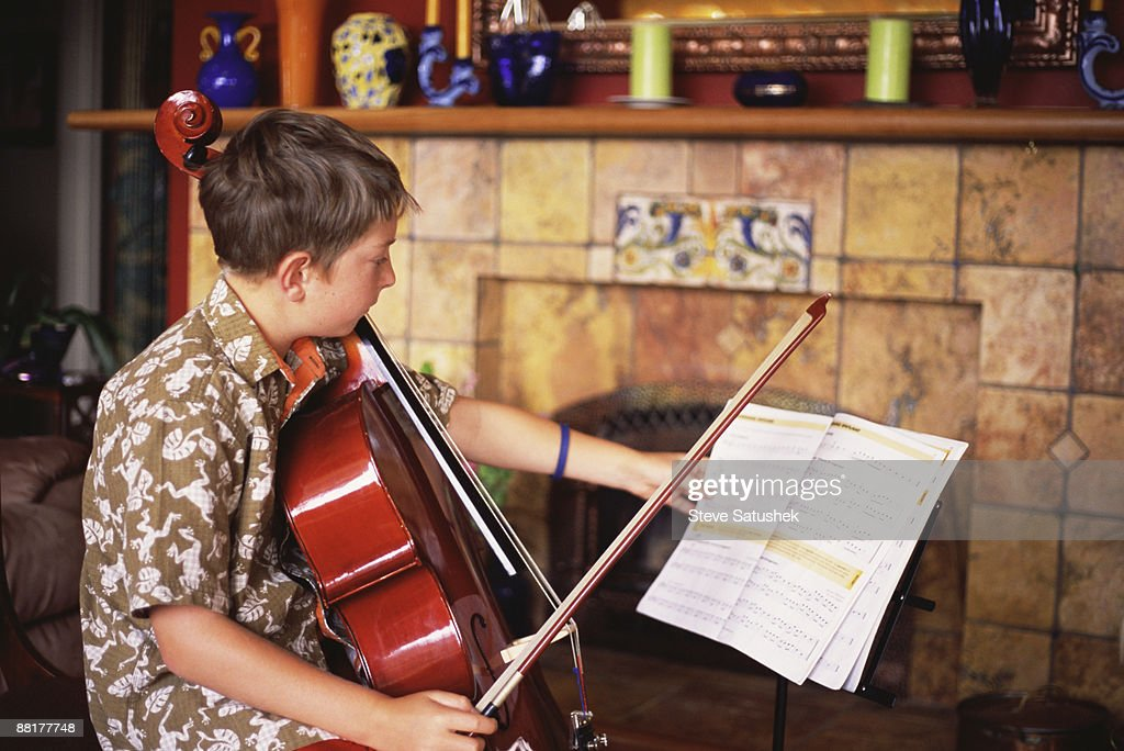 Boy practicing cello : Stock Photo