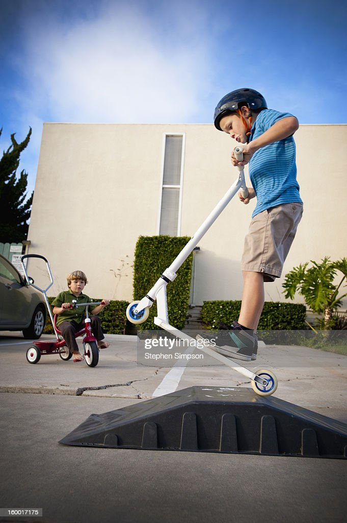 boy practicing jumps on his sidewalk scooter : Stock Photo