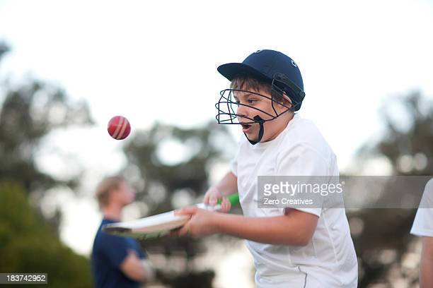Boy practising hitting cricket ball with bat