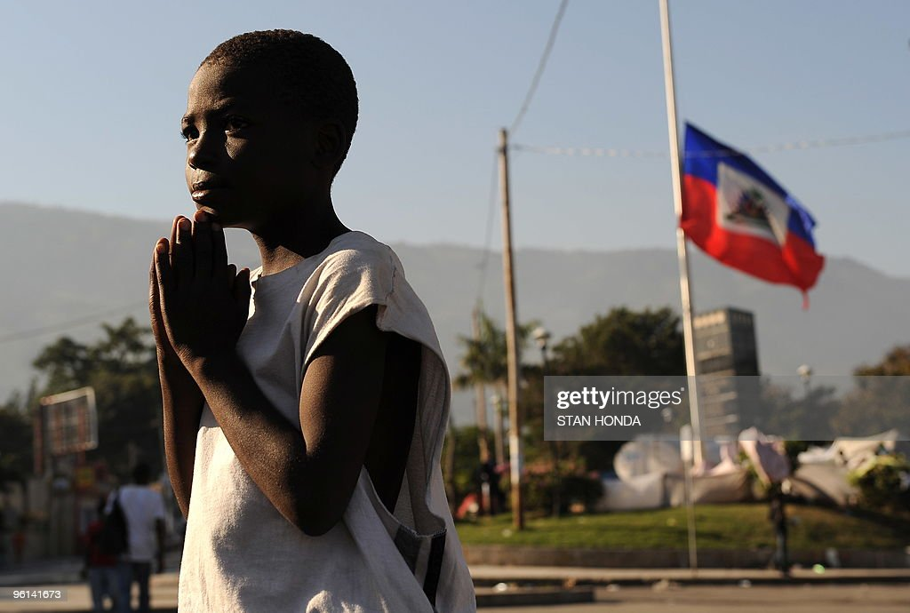 A boy prays by a Haitian flag flying at halfmast in Champ de Mars in Port-au-Prince on January 24, 2010. More than 110,000 people have been confirmed as killed in Haiti's devastating earthquake, the Interior Ministry said, making it the deadliest on record in the Americas. AFP PHOTO / STAN HONDA