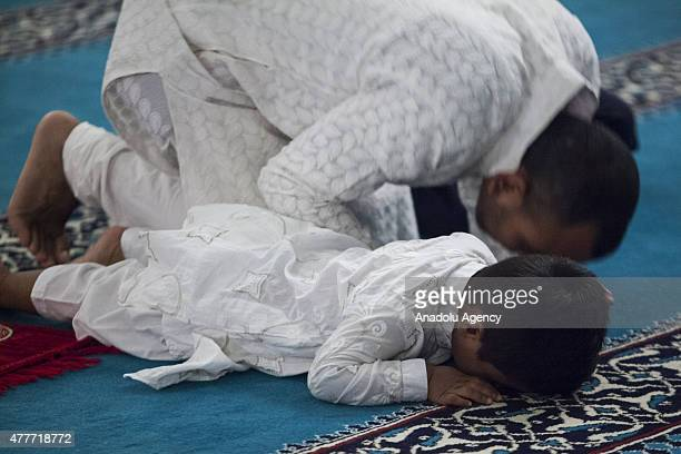 A boy prays with his father in the mosque at the Turkish American Community Center in Lanham Maryland on the first day of Islam's holy fasting month...