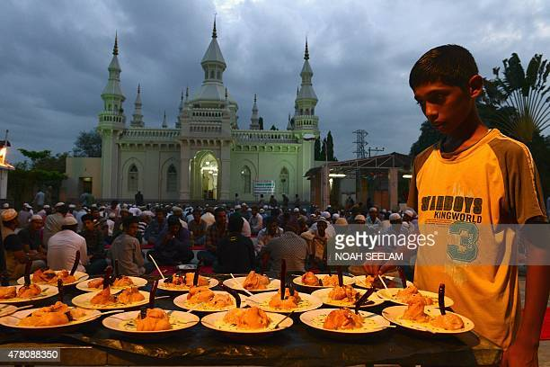 A boy prepares food prior to Indian Muslim devotees breaking their fast on the Islamic holy month of Ramadan at the JamaeMasjid Aiwan in Hyderabad on...