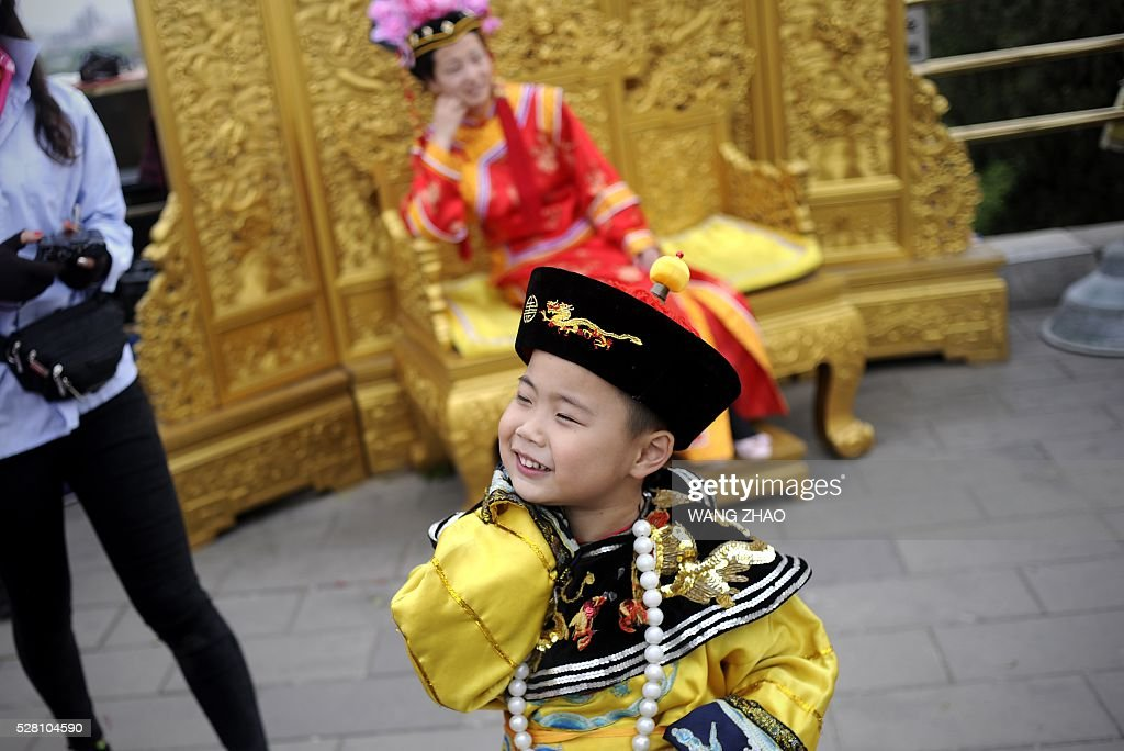 A boy prepares to wear a costume of a Qing dynasty emperor for a portrait session at a park near the Forbidden City in Beijing on May 4, 2016. / AFP / WANG
