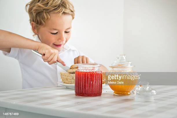 A boy preparing a jelly sandwich