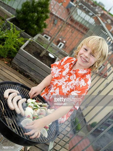 Boy (8-9) preparing barbecue, smiling, portrait