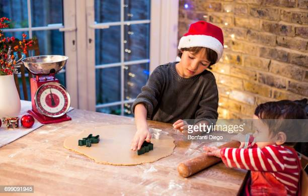 Boy preparing Christmas cookies with baby brother at kitchen counter