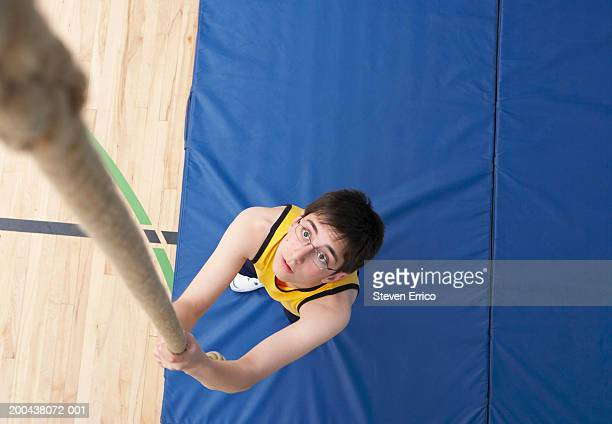 Boy (11-13) preparing to climb rope in school gymnasium, elevated view