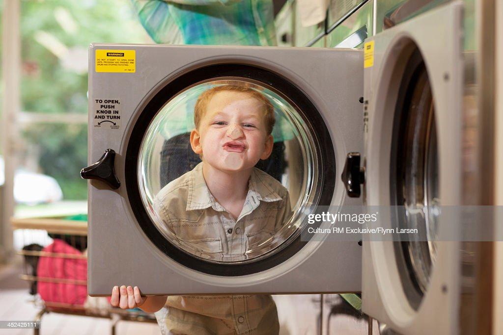Boy pressing face against washing machine door : Stock Photo