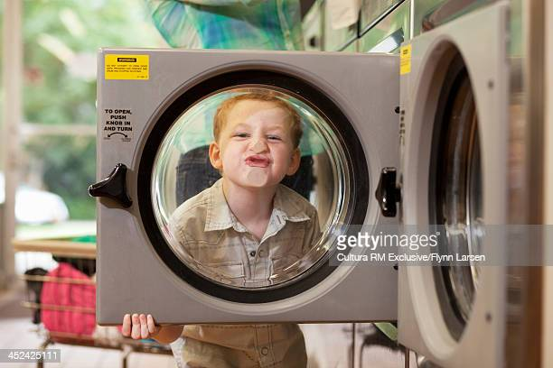 Boy pressing face against washing machine door
