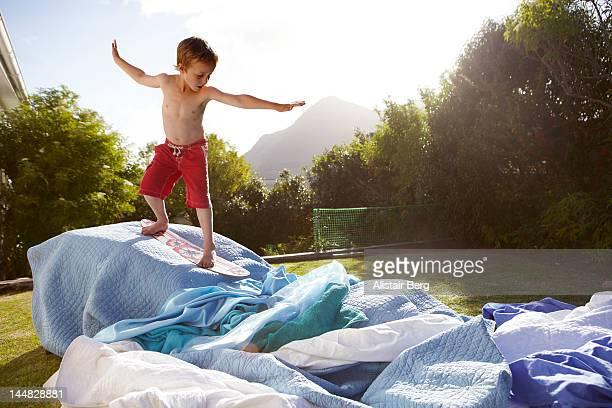 Boy pretending to be a surfer in a suburban garden