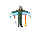 Creative original smart boy in pilot uniform playing with jetpack crafted toy, Isolated on white background, Future dreams and imagination concept