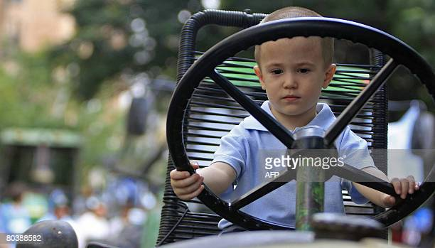 A boy pretends he drives a tractor during a demonstration of the farming world against against Argentine president Cristina Fernandez de Kirchner for...